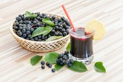 Fresh juice of chokeberry or Aronia melanocarpa in glass and berry in pot on wooden stock image