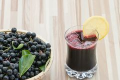 Fresh juice of chokeberry or Aronia melanocarpa in glass with ice and lemone slice, berry in basket royalty free stock photo
