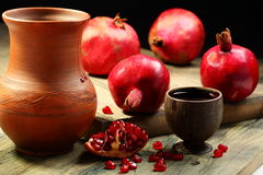 Fresh juice in cup and ripe pomegranates. Stock Photography