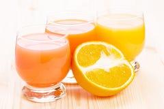 Fresh juice with cut in half orange fruit Royalty Free Stock Photo