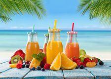 Fresh juice with fruit mix on the beach. Fresh glasses of juice with fruit mix placed on the beach on wooden planks. Concept of healthy drinks, antioxidants and Stock Image
