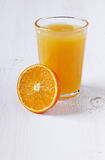 Fresh juice in a glass with an orange half. On a wooden white surface Royalty Free Stock Photo