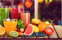 Glasses of fresh juice on white background