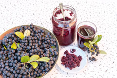 Fresh juice and jam of black chokeberry Aronia melanocarpa in glass and berry in pot on white textured background stock photo
