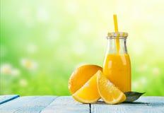 Fresh juice with orange fruit on wooden table Royalty Free Stock Image