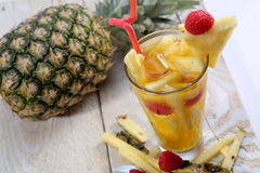 Fresh juice with pineapple slice. A glass of fresh juice with pineapple slice on a side and a pineapple fruit on the table Royalty Free Stock Photos