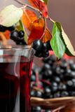 Fresh juice of ripe black chokeberry in glass and berries with l stock photo