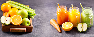 Fresh juice and smoothies with fruits and vegetables. On dark table stock photography