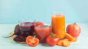 Fresh juice smoothies from a variety of vegetables beetroot apple carrot tomatoes in glasses on wooden blue background. Fresh juice smoothies from a variety of royalty free stock images