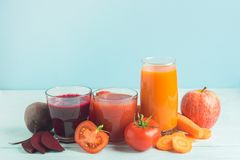 Fresh juice smoothies from a variety of vegetables beetroot apple carrot tomatoes in glasses on wooden blue background. stock photo