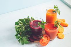 Fresh juice smoothies from a variety of vegetables beetroot apple carrot tomatoes in glasses on wooden blue background. royalty free stock photos