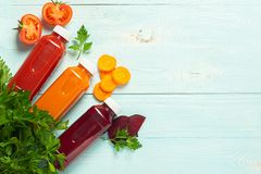 Fresh juice smoothies from a variety of vegetables carrots apple tomatoes beets in bottles on a wooden blue background. Top view flat layout. Copy space stock images