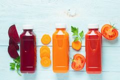 Fresh juice smoothies from a variety of vegetables carrots apple tomatoes beets in bottles on a wooden blue background. Top view flat layout. Copy space royalty free stock image