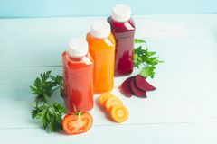 Fresh juice smoothies from a variety of vegetables carrots apple tomatoes beets in bottles on a wooden blue background. Selective focus. Copy space. Horizontal stock photos