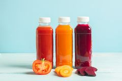 Fresh juice smoothies from a variety of vegetables carrots apple tomatoes beets in bottles on a wooden blue background. Selective focus. Copy space. Horizontal stock images