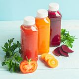 Fresh juice smoothies from a variety of vegetables carrots apple tomatoes beets in bottles on a wooden blue background royalty free stock photos