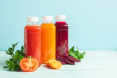 Fresh juice smoothies from a variety of vegetables carrots apple tomatoes beets in bottles on a wooden blue background. Selective focus. Copy space. Horizontal stock image