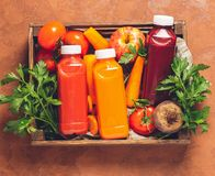 Fresh juice smoothies from a variety of vegetables carrots apple tomatoes beets bottles in wooden box brown background. Fresh juice smoothies from a variety of royalty free stock images