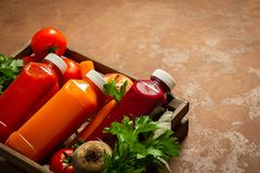 Fresh juice smoothies from a variety of vegetables carrots apple tomatoes beets bottles in wooden box brown background. Fresh juice smoothies from a variety of stock photos