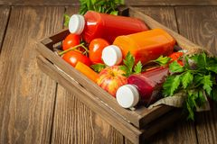 Fresh juice smoothies from a variety of vegetables carrots apple tomatoes beets bottles in wooden box brown background. Fresh juice smoothies from a variety of stock images