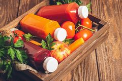 Fresh juice smoothies from a variety of vegetables carrots apple tomatoes beets bottles in wooden box brown background. royalty free stock photos