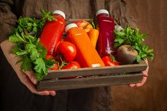 Fresh juice smoothies from various vegetables carrot apple beet tomatoes in bottles in a wooden box in female hands stock photo