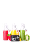 Fresh juice in summer. Some juice bottles of different colors with fresh fruits on a white background Stock Photo