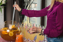 Fresh juice on a table in a restaurant. Healthy drinks. carrot fresh in a jar. Girl pouring juice Stock Photography