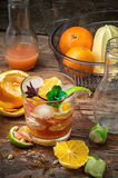 Fresh juice of tropical citrus fruits on wooden background Royalty Free Stock Images