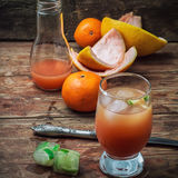 Fresh juice of tropical citrus fruits on wooden background Stock Images