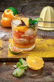 Fresh juice of tropical citrus fruits on wooden background Royalty Free Stock Photos