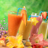 Fresh Juices. Fresh papaya, mango, strawberry and pineapple fruit juices and milkshakes decorated with flowers (Selective Focus, Focus on the papaya juice and Stock Photos