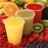 Fresh juices. Cups with different kinds of juices surrounded by fresh fruits royalty free stock photos