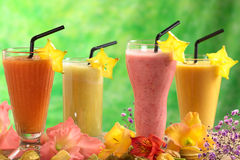 Fresh Juices and Milkshakes. Fresh papaya, strawberry, pineapple and mango fruit juices and milkshakes decorated with flowers (Selective Focus, Focus on the royalty free stock photography