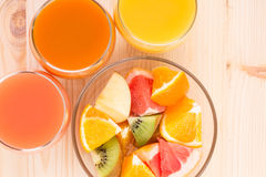 Fresh juices in three glasses with fruit salad. Stock Images
