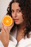 Fresh an Juicy. Young brunette woman holding half a orange stock image