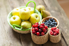 Fresh juicy apples, pears and berries on a wooden table Stock Photography