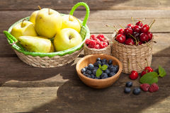 Fresh juicy apples, pears and berries on a wooden table Stock Images