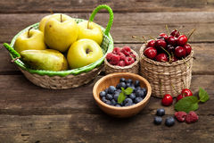 Fresh juicy apples, pears and berries on a wooden table Royalty Free Stock Image