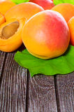 Fresh juicy apricots. Scattered on the wooden background Stock Photo