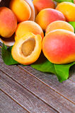 Fresh juicy apricots. Scattered on the wooden background Stock Image