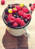 Fresh juicy berries, raspberries, currants, blackberries, a gooseberry in an old white iron mug. On a wooden surface Royalty Free Stock Photos