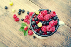 Fresh juicy berries, raspberries, currants, blackberries, a gooseberry in an old white iron mug. On a wooden surface Stock Images