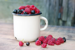 Fresh juicy berries, raspberries, currants, blackberries, a gooseberry in an old white iron mug. On a wooden surface Stock Photography