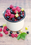 Fresh juicy berries, raspberries, currants, blackberries, a gooseberry in an old white iron mug. On a wooden surface Royalty Free Stock Photo