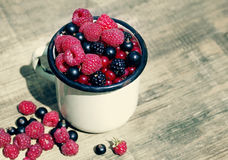 Fresh juicy berries, raspberries, currants, blackberries in an old white iron mug. On a wooden surface, close up Stock Photo