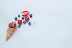 Fresh juicy berries and sweet waffle cone on the blue background, top view Royalty Free Stock Images