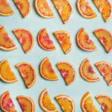 Fresh juicy blood orange slices over blue background, square crop Royalty Free Stock Photography