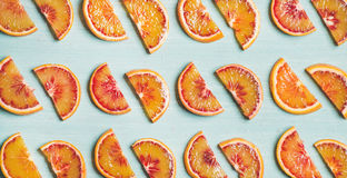Fresh juicy blood orange slices over blue background, wide format Stock Photography