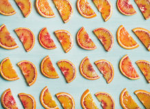 Fresh juicy blood orange slices over blue painted table background Stock Photos